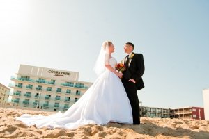 bride and groom on beach in front of marriott